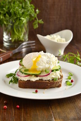 Sandwich with cream cheese, radish, cucumber and poached egg