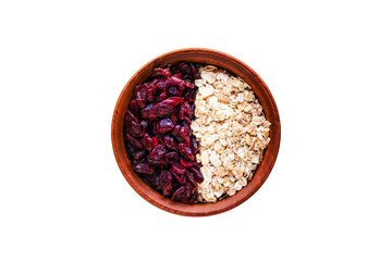 Raw oatmeal with dried cranberries in a round clay bowl on a dark wooden background. Healthy fitness vegetarian breakfast granola meal with cranberries. Top view
