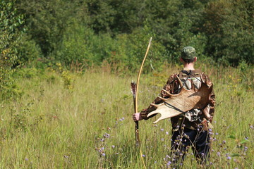 Archer hunter in summer field with a bow, arrows and an elk horn, a text space background design pattern