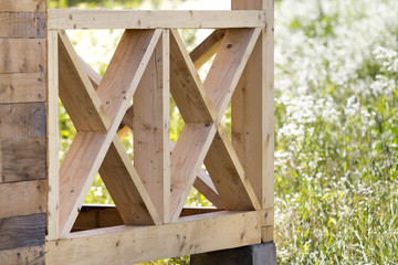 Close-up section geometrical decorative simple detail of new natural not painted wooden planks and bars for balcony, attic fence on blurred blooming summer field background. Construction and design.
