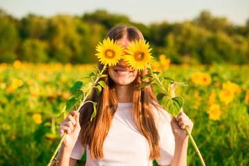 Happy joyful girl with sunflower enjoying nature and laughing on summer sunflower field