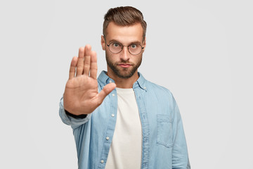 Serious European male shows stop gesture, demands something, has strict facial expression, wears round spectacles and formal shirt, isolated over white background. People and body language concept