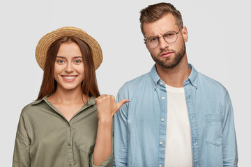 Horizontal shot of pretty female traveller in straw hat has broad shining smile, points at her boyfriend who has dissatisfied expression, spend free time together, pose against studio background