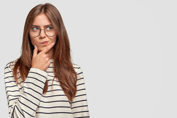 Confused lovely female teenager holds chin, looks thoughtfully aside, has dark hair, wears striped sweater, isolated over white background with copy space for advertisement. Thoughtful woman indoor