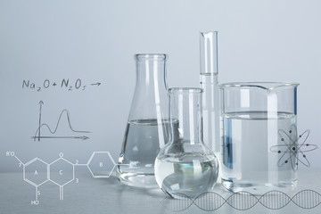 Laboratory glassware with liquids for analysis on table and chemical formulas against light background