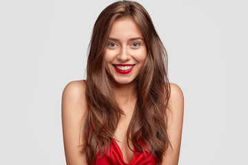 Beauty, fashion, makeup and people concept. Lovely happy woman with red lipstick, shows white perfect teeth, has healthy skin, long dark hair, isolated over white background, expresses happiness