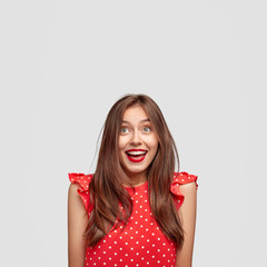 Joyful pretty female with red lipstick, wears elegant polka dot summer dress, looks positively upwards, hears friends voice upstairs, isolated over white background. People, fashion and makeup concept