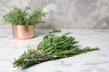 Bunch of fresh rosemary on marble table. Aromatic herbs