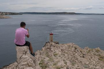 Croazia: uomo di spalle fotografa il piccolo faro rosso sulla scogliera di fronte al Paški Most, il ponte del 1968 che collega la Croazia con l'isola di Pag