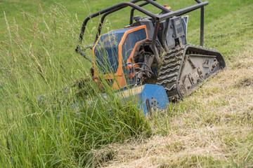 Robot mows meadow on hillside