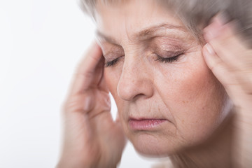 Seniorin woman with gray hair headache pain