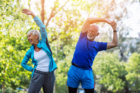 Happy fit senior couple exercising in park.