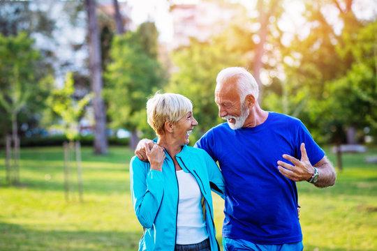 Happy senior couple enjoying in walk outdoors in park.