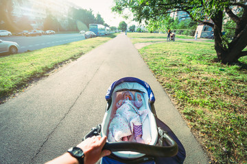 Father is walking with his baby on the street in town.Cute baby baby girl pacifier lies in baby carriage.