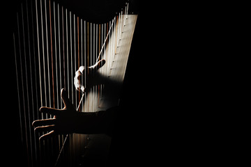 In de dag Muziek Harp player. Hands playing Irish harp strings