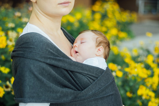 Mother carrying sleeping baby in sling, attachment parenting concept