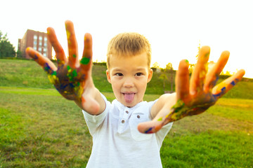 cheerful child shows that his hands are painted with colorful paints