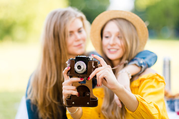 Cheerful girls in the cottage garden with vintage camera. Family and friends autumn fall holidays