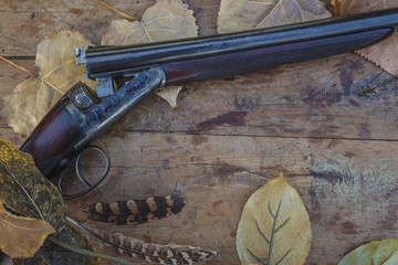Beautiful hunting gun, pheasant feathers and dry autumn leaves on old wooden background with copy space