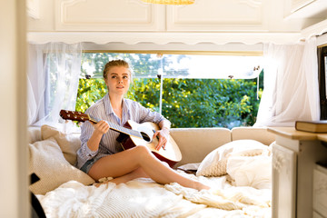 Beautiful girl in a camper van, with a guitar. Road trip with best friends. Adventure, freedom, youth