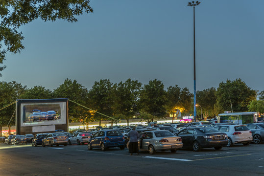 city parking with an inflatable screen of a summer cinema, waiting for a movie