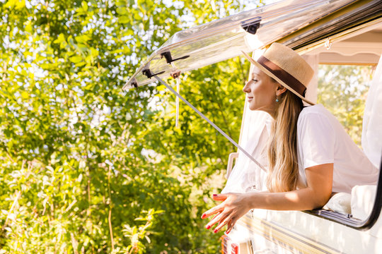 Cheerful pretty girl in a van window in nature. Traveling with friends, freedom, road trip