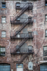 Worn brick building with metal fire escape