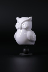 Owl a decorative figure, from different materials, against a dark background.