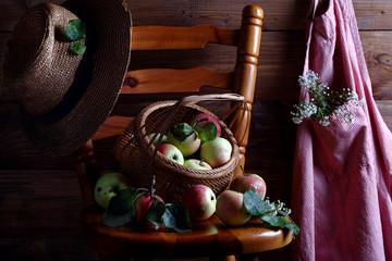 спелые яблоки в плетеной корзине на деревянном стуле