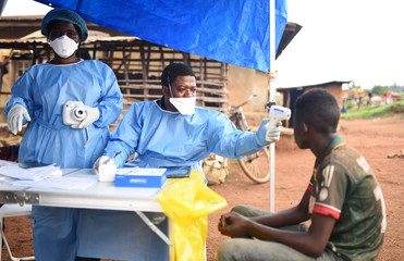 Congolese health workers take the temperature of a civilian before administering the Ebola vaccination in the village of Mangina