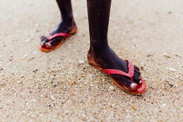 Feet of a Black Man in Red Flip Flops Standing on Sandy Beach