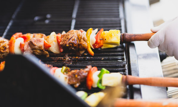 colorful barbecue stick on charcoal stove with chef's hand wearing glove holding wooden handle