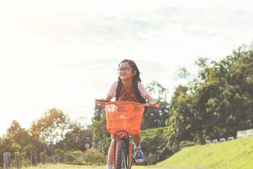 cute little girl riding bike go to school