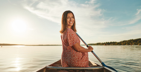 Smiling young woman paddling her canoe on a sunny day