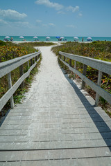 Dramatic vertical view of Wood Bridge looking toward a Sandy Ocean Beach with Colorful Umbrellas on a Sunny Day