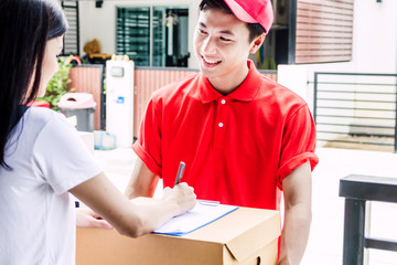 Woman putting signature in clipboard on cardboard box with delivery man.courier service concept