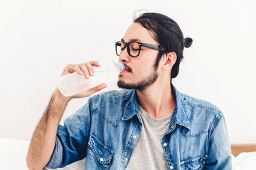 Healthy young man drinking water from a bottle  while relaxing and feeling fresh at home