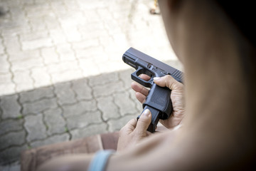 This girl is preparing a gun for use in drills,loading bullets in gun.