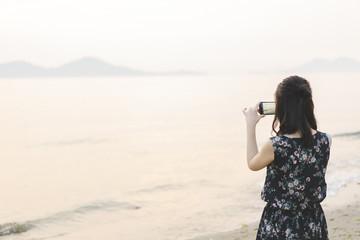 夕暮れの海で写真を撮る女性