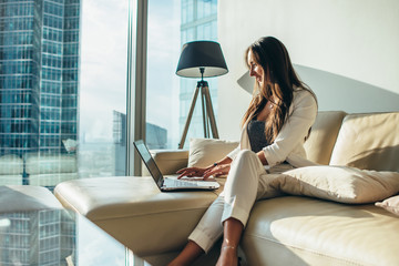 Young female business woman using a laptop sitting on a sofa at home