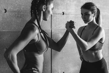 Fit women holding hands with a female opponent looking in her eyes.