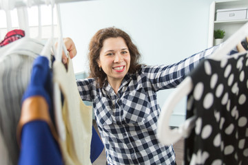 Wardrobe, clothes, people concept - woman choosing clothes to wear in her wardrobe