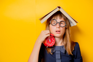 Portrait of a nerd girl in glasses with books and alarm clock on yellow background