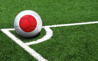 soccer ball on a green field, flag of Japan