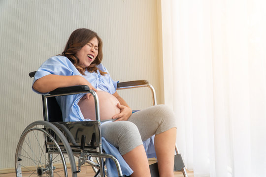Portrait A pregnant woman sitting on a wheelchair near the balcony. She has very abdominal pain. She needs help And want to see a doctor. Copy space.