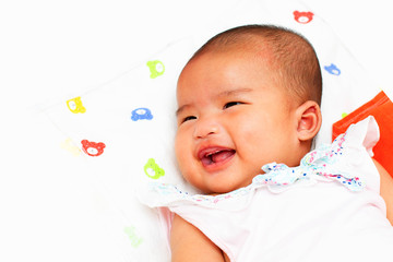 Smiling newborn infant baby girl on white bed