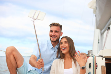 Happy couple taking a selfie after engagement proposal at sailing boat, relaxing on a yacht at the sea.