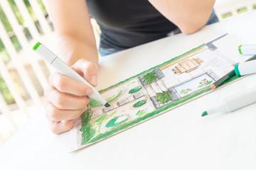 Gasrtenplanung: Gartenarchitektin zeichnet einen Gartenplan für einen kleinen Hausgarten