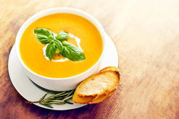 Squash soup with on wood table. Autumn Pumpkin soup served in a bowl, top view. Copy space.