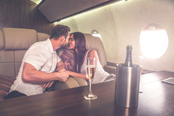 Couple on vacation, flying on their private jet Wall mural